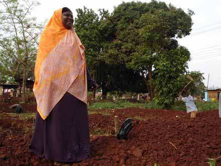 Mariam Yahya of Jinja stands on her plot as construction begins on her Parsons-designed model home,