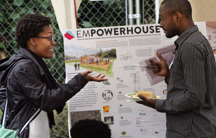 Solar Decathlon team member Obinna Elechi, a Parsons Architecture student (right), speaks with community member