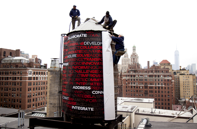 Crew members wrap the water tower on top of the building at 66 West Fifth Ave to reflect the university's new visual identity. Designed by Parsons Art Media and Technology students Rafael Cordoba and Joe Evans for their University Design Studio course. Photo by Kasia Broussalian/The New School.