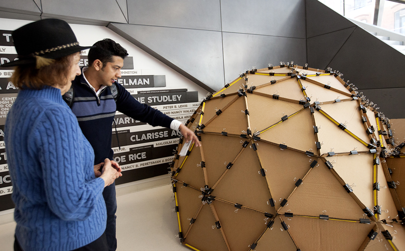 Students and faculty discuss features of the Dome of Memory, a geodesic dome constructed of corrugated cardboard and binder clips, during The New School's Earth Day celebration at the University Center. Photo by Kasia Broussalian/ The New School.