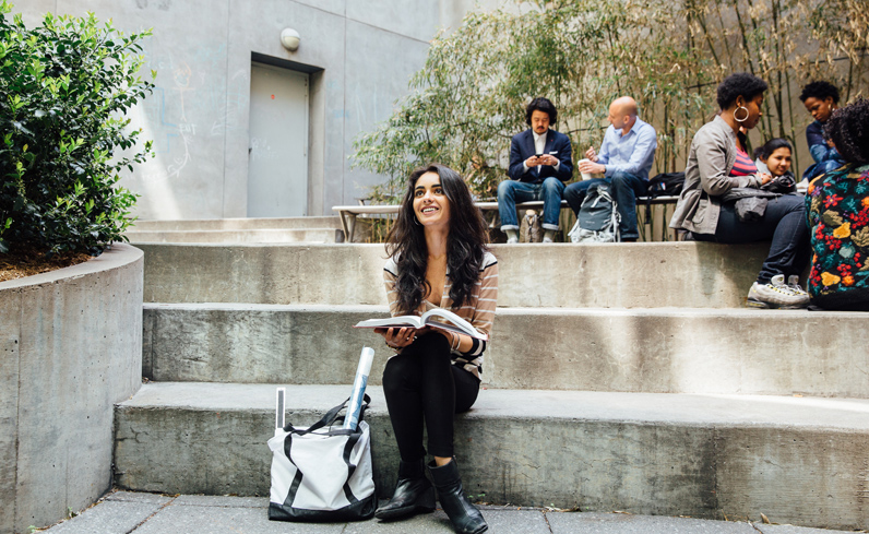 A student taking continuing education classes lounges on the steps of the Vera List Courtyard at 66 West 12th Street.