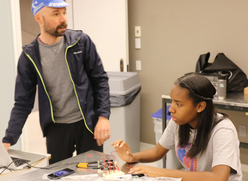Ryan Raffa, a a part-time lecturer at Parsons who leads the Creative Technology Course, instructs student Noelia Baptista on the design process.